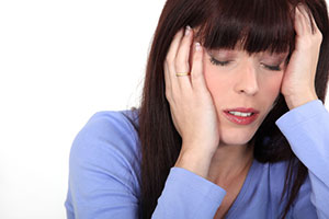 Woman with a bad headache, holding her head