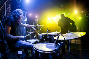 musicians in a rock band playing guitars and drums